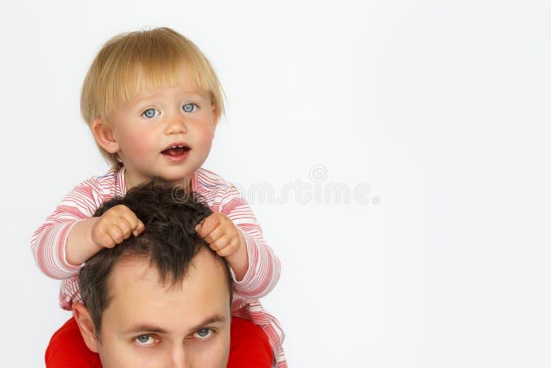 Behandla som ett barn sammanträde på faderhals på vit bakgrund arkivbilder