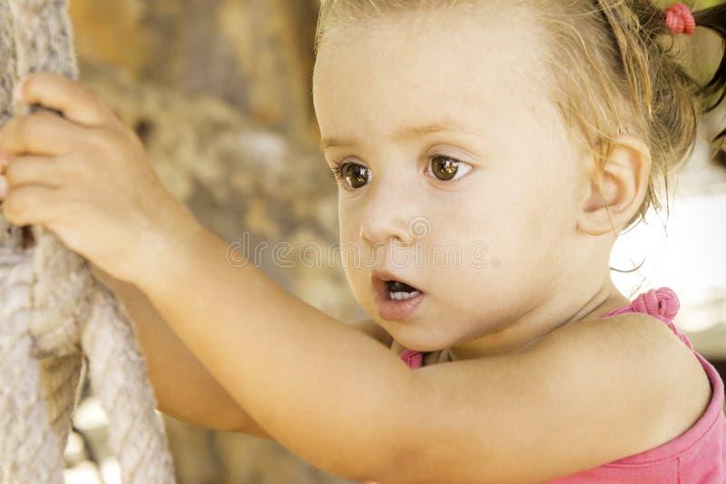 Behandla som ett barn sammanträde på gunga och att se av in i avståndet royaltyfria foton