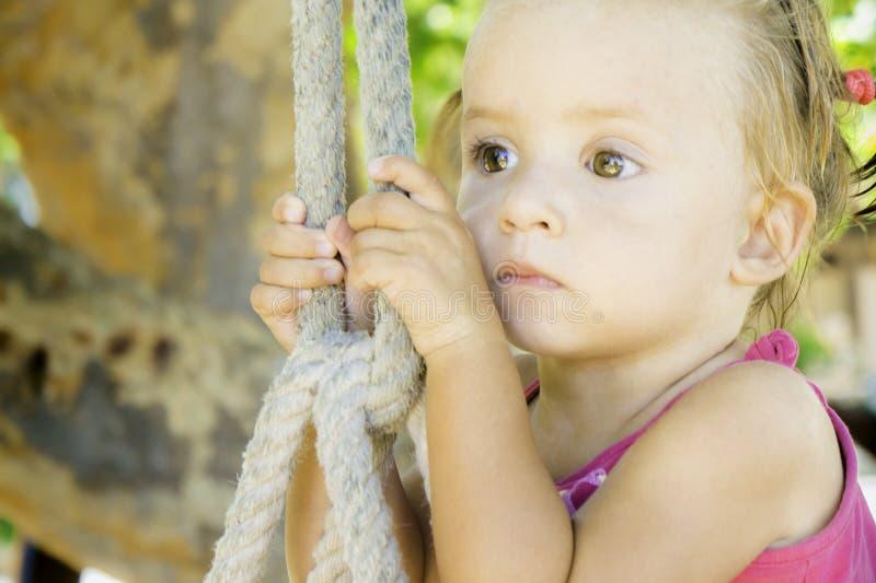 Behandla som ett barn sammanträde på gunga och att se av in i avståndet hon har mycket härliga ögon arkivfoton