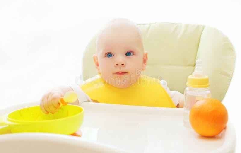 Behandla som ett barn sammanträde på tabellhemmet och äter skeden royaltyfria foton
