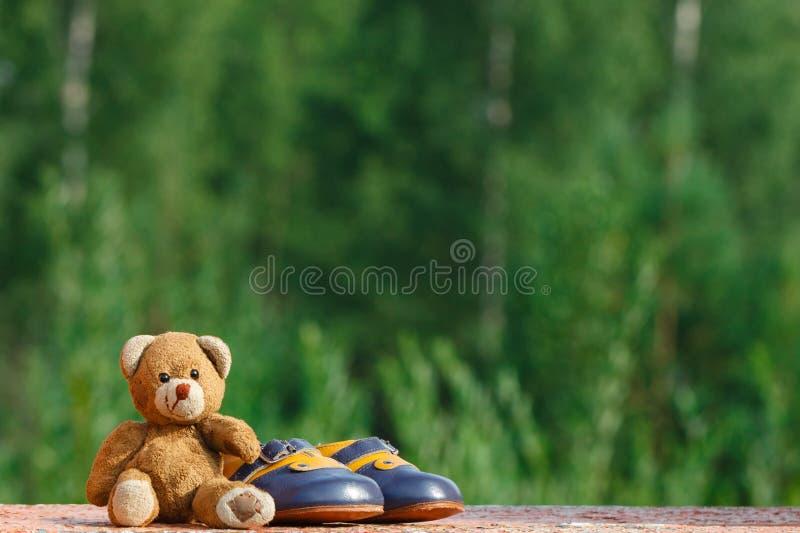 Behandla som ett barn skor med nallebjörnen royaltyfria foton