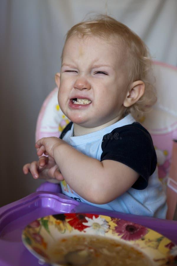 Behandla som ett barn skrik och vägrar att äta soppa Den lilla vita pojken vinkar hans hand i väg från maten arkivfoto