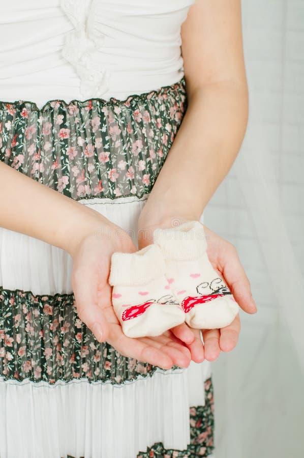 Behandla som ett barn sockor i händer av gravida kvinnan royaltyfri foto