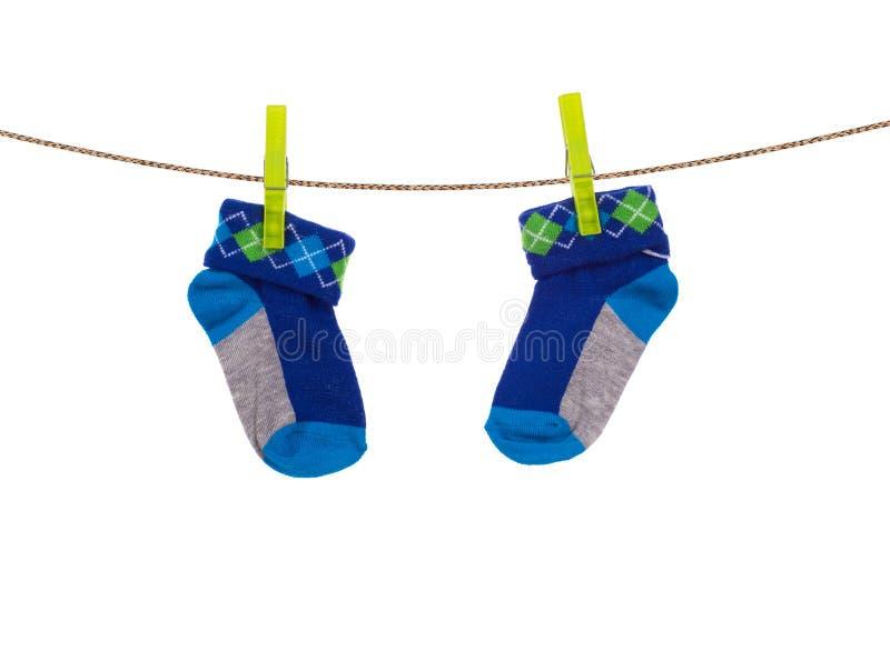 Behandla som ett barn sockor som hänger på en klädstreck arkivfoton