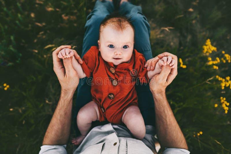 Behandla som ett barn spädbarnet på fader knäa utomhus lycklig familjlivsstil royaltyfria bilder