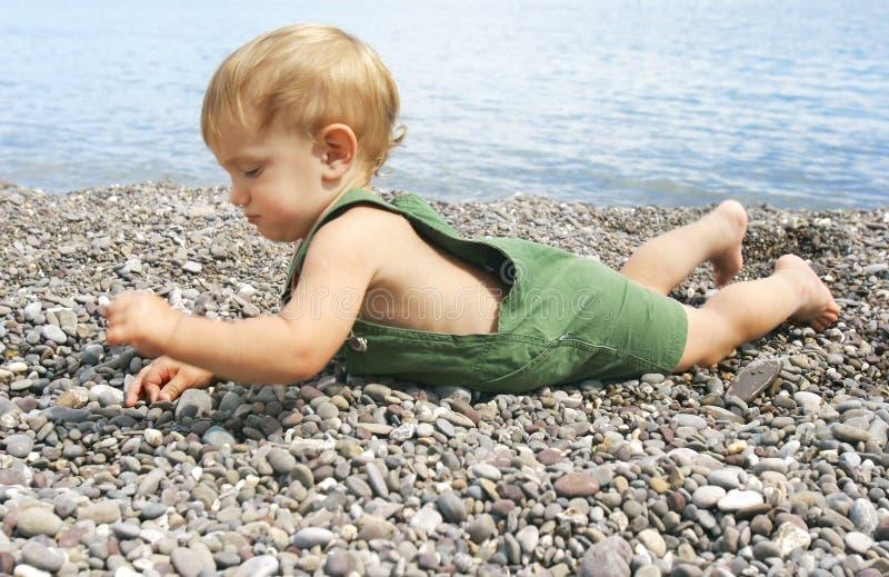 behandla som ett barn strandpebblen arkivfoto
