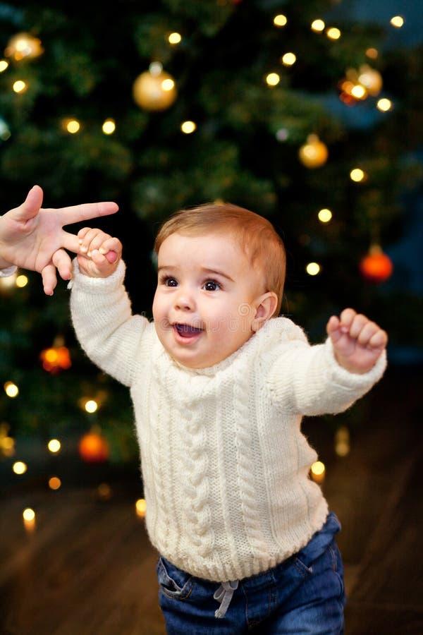 Behandla som ett barn tagandeförsta steg som rymmer hennes mother& x27; s-hand på bakgrunden av julgranen royaltyfria foton