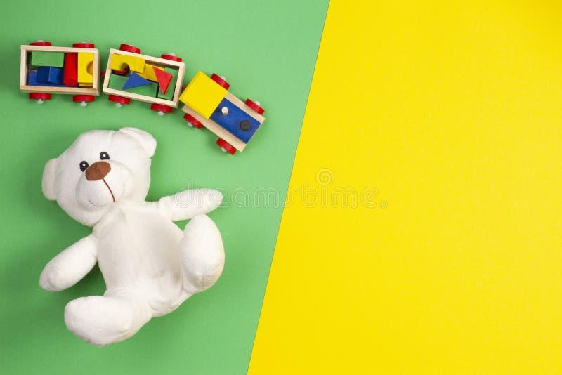 Behandla som ett barn ungeleksakbakgrund Vit nallebjörn och träleksakdrev på mångfärgad gul och grön bakgrund arkivbilder