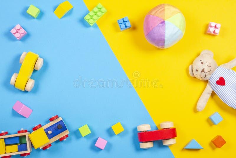 Behandla som ett barn ungeleksakramen med nallebjörnen, träleksakdrevet, bilen, färgrika tegelstenar på blått och gulna bakgrund  arkivbilder