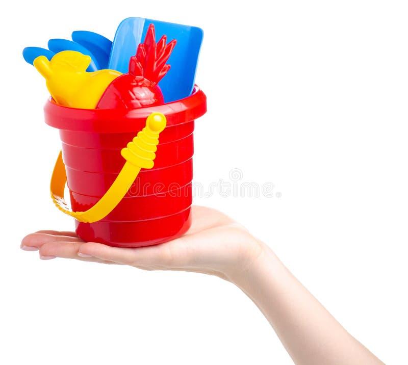 Behandla som ett barn uppsättningen som den röda sandlådahinkskyffeln krattar leksaken i hand arkivfoton