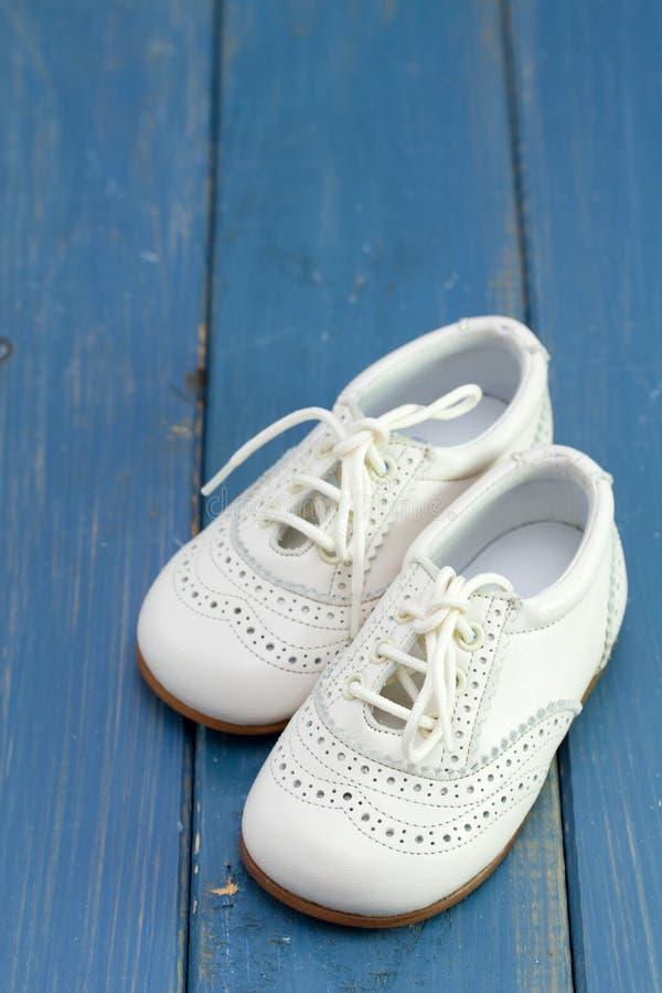 behandla som ett barn vita skor arkivbild