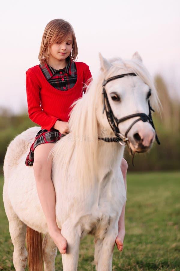 Behandla som ett barnflickan sitter på en fundersam ponny royaltyfria foton
