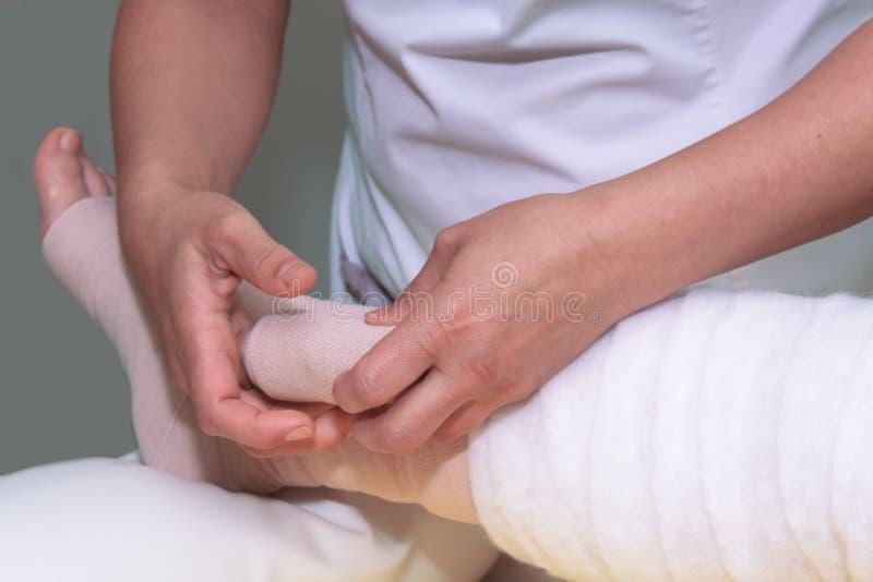 Behandling av lymfom: Svällningsben med multilagerförband för att kontrollera lymfom En del av fullständig degestiv behandling ka royaltyfri foto