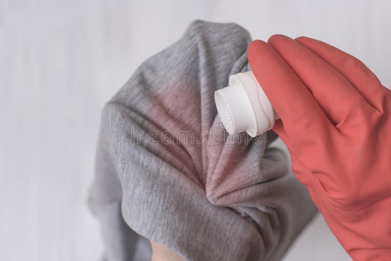 Behandschuhte Hand, welche die Waschenflüssigkeit auf den Fleck auf Kleidung gießt Abschluss oben lizenzfreies stockbild