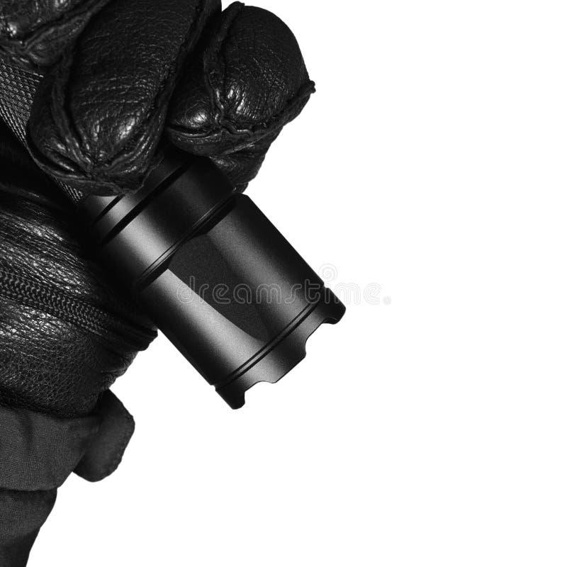 Behandskad hand som rymmer den taktiska ficklampan, ljust ljus som ljust sänder ut liten, göra ett hack i slagskyddsram, svart ko fotografering för bildbyråer
