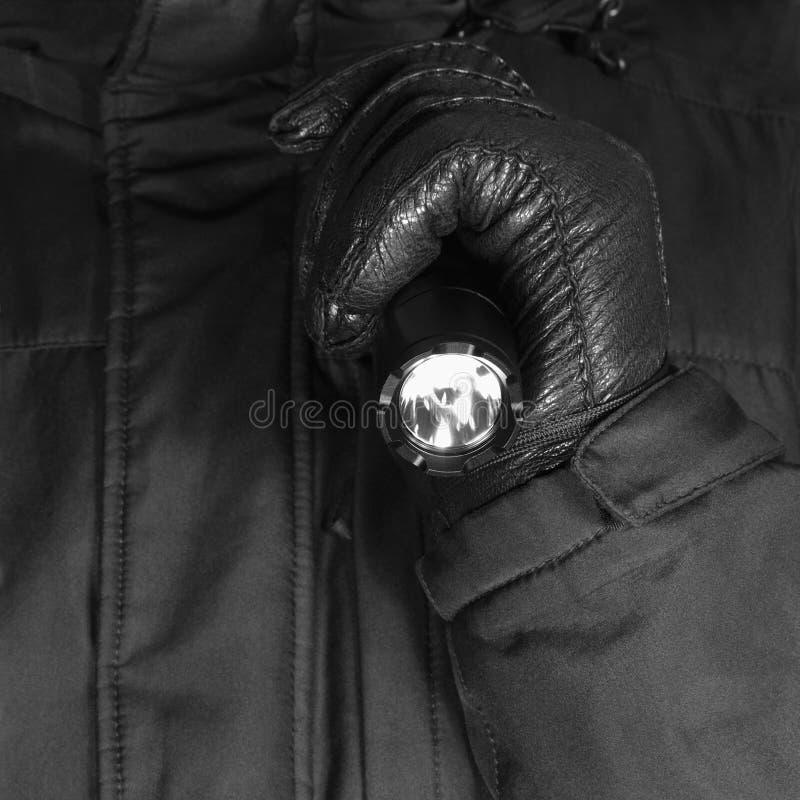 Behandskad hand som rymmer den taktiska ficklampan, ljust ljus som ljust sänder ut liten, göra ett hack i slagskyddsram, svart ko arkivbilder