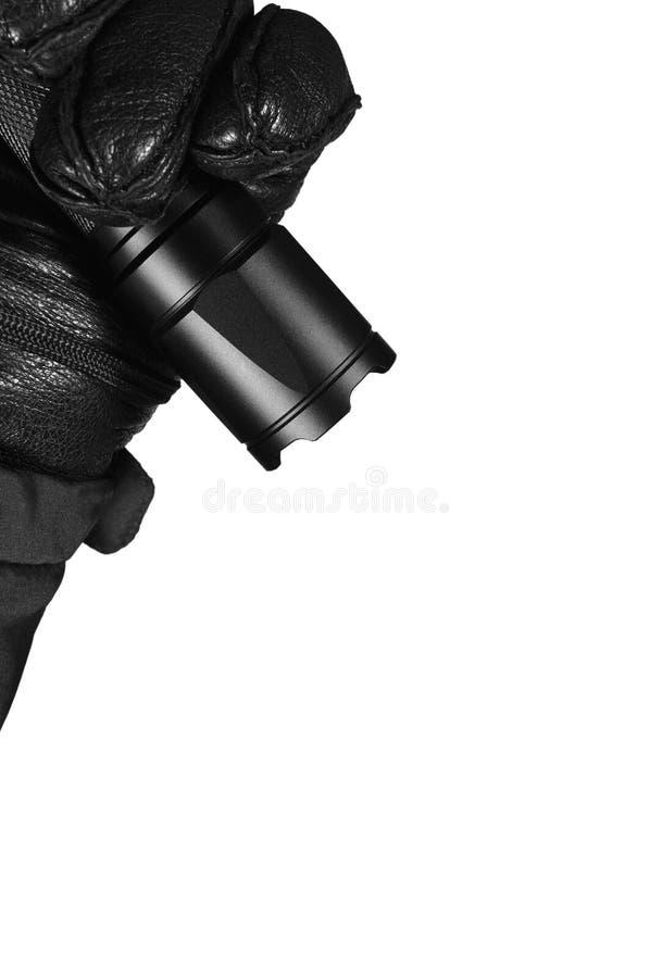 Behandskad hand som rymmer den taktiska ficklampan, ljust ljus som ljust sänder ut liten, göra ett hack i slagskyddsram, svart ko royaltyfri foto