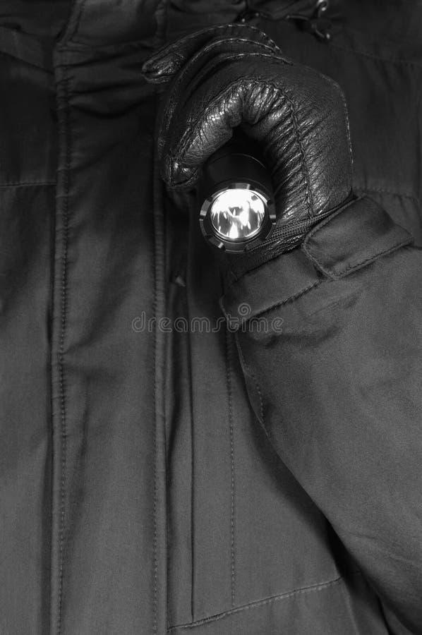 Behandskad hand som rymmer den taktiska ficklampan, ljust ljus som ljust sänder ut liten, göra ett hack i slagskyddsram, svart ko royaltyfri bild