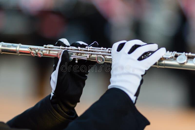 Behandskade händer av en flöjtspelare i en marschmusikband arkivfoton
