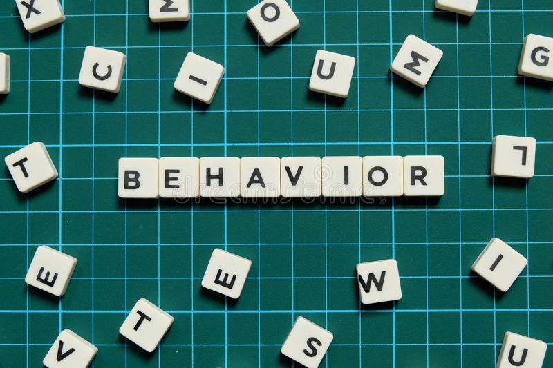 Behavior word made of square letter word on green square mat background. Behavior word made of square letter word on green square mat background royalty free stock photos