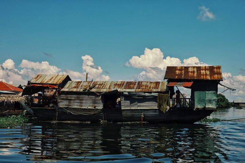 behelfsmäßiges sich hin- und herbewegendes Boot wie Wohnungsbau mitten in dem überschwemmten See lizenzfreie stockbilder