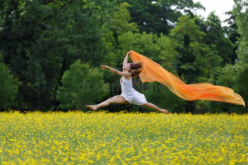 Behendige vrouw die in de lucht springen royalty-vrije stock afbeelding