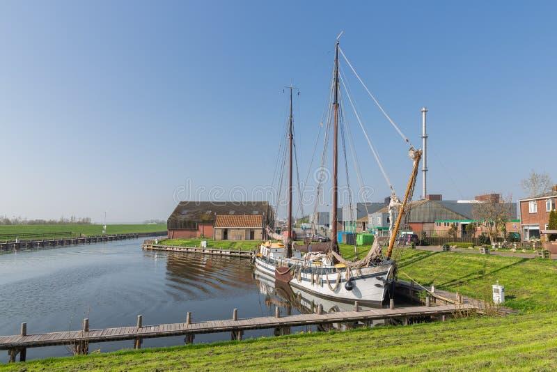 Beherbergten Sie mit hölzernem Segelschiff im niederländischen Fischerdorf Workum stockbild