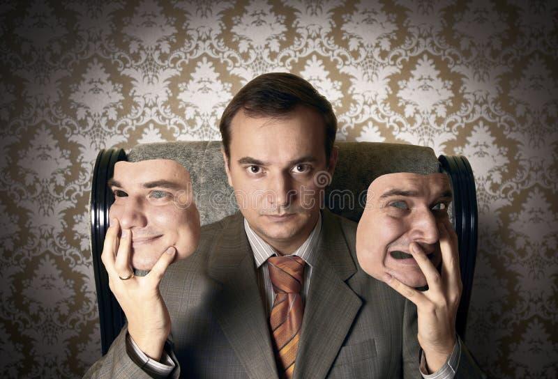 Beherrschen Sie das Sitzen auf dem Lehnsessel und seine Gesichtsmasken halten lizenzfreies stockfoto