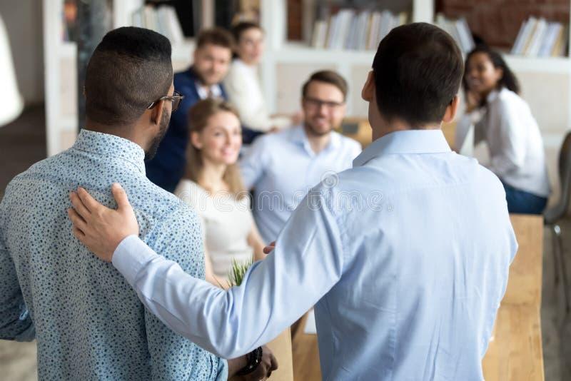 Beherrschen Sie das Vorstellen der schwarzen neuen Arbeitskraft zu den Workmates stockfotos