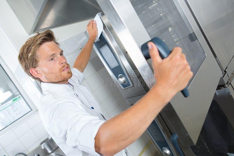 Behilfliche Reinigungsküche des hübschen Chefs mit Lappen stockbilder