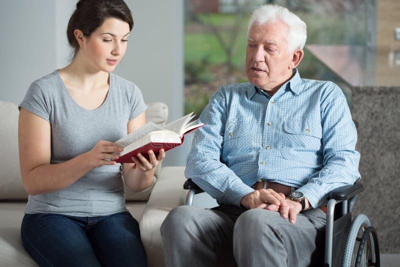 Behilfliches Buch der Seniorenbetreuung Lese stockbild
