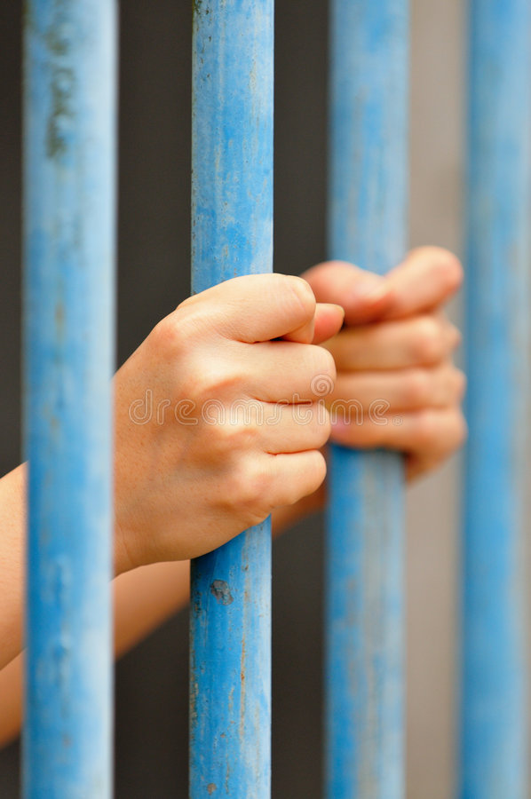 Behind Bars 2. An image of a person behind bars royalty free stock image