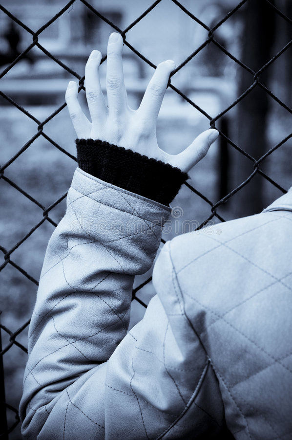 Behind bars. Hands grabbing prison bars in blue stock photo