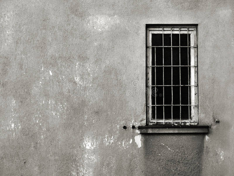 Behind the bars. Single dark window with grating on a decaying wall. Black and white image with copy space stock photos