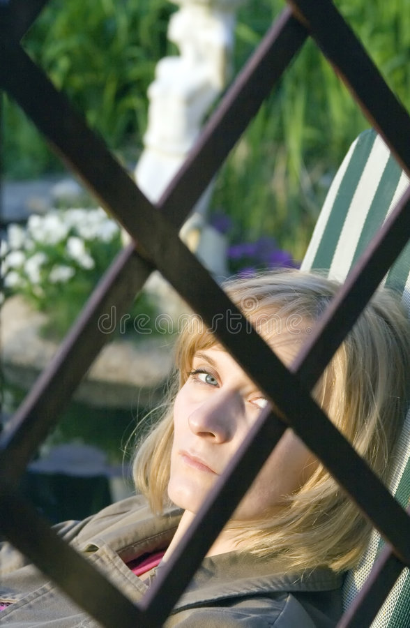 Behind bars. Woman behind the wooden bars in the garden stock images