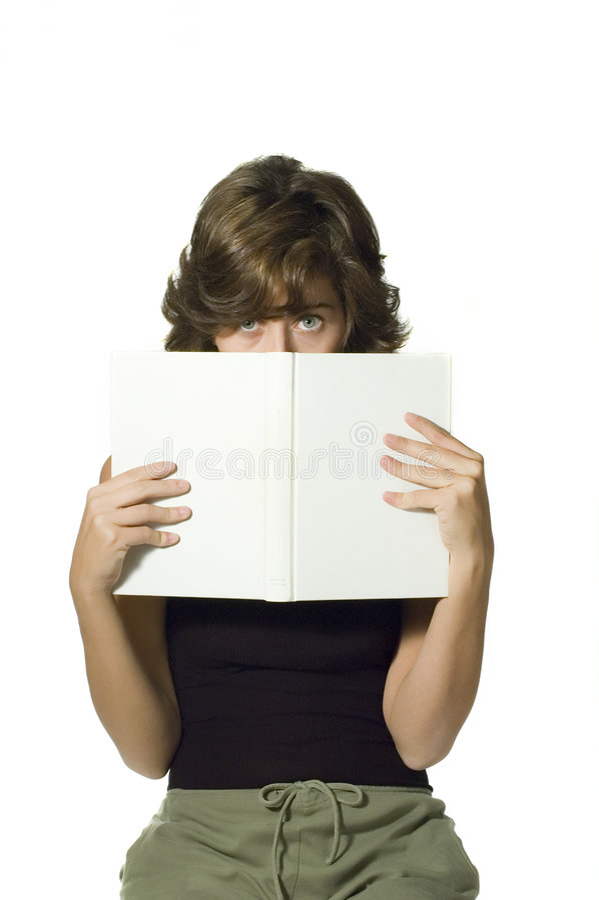 Behind a book. Shy girl reading stock photos