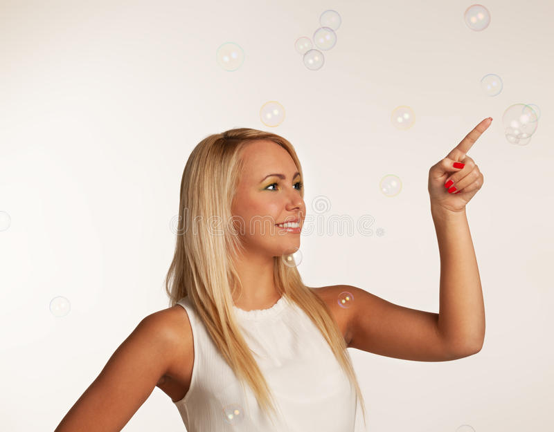 Behind the bubbles. Girl playing with soap bubbles royalty free stock images