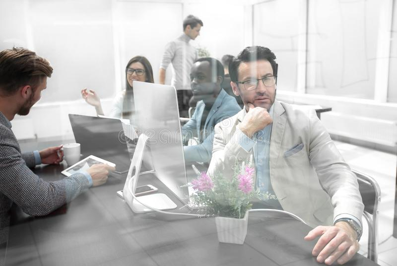 Behind the glass.business team in the office royalty free stock images