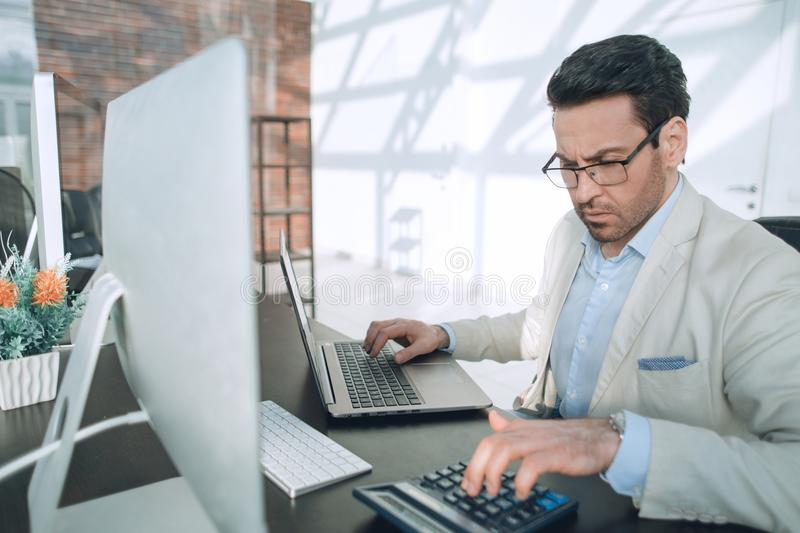 Behind the glass.serious businessman analyzing financial data. royalty free stock photography