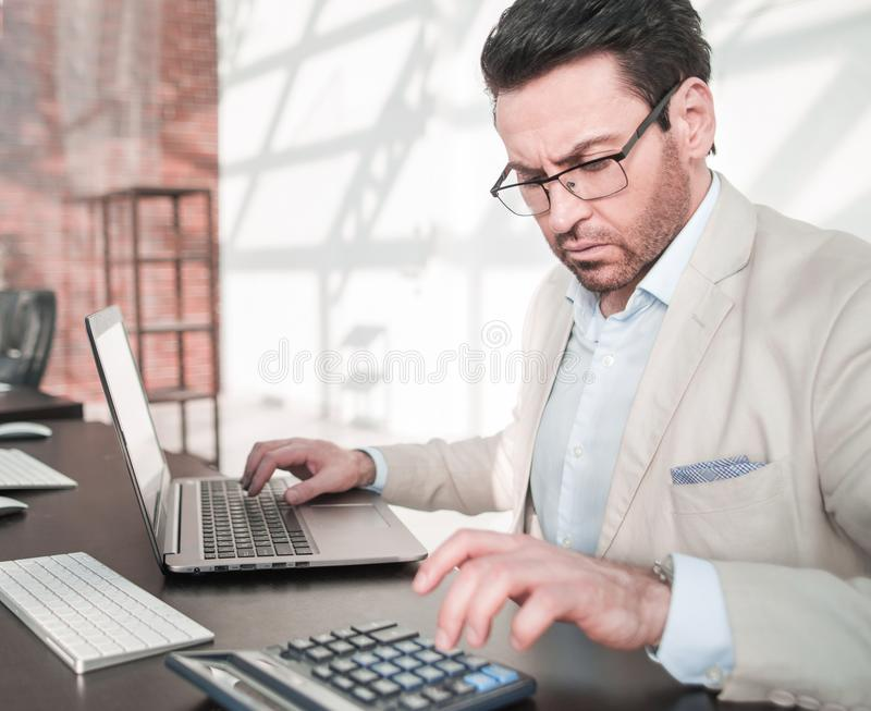 Behind the glass.serious businessman analyzing financial data. stock images