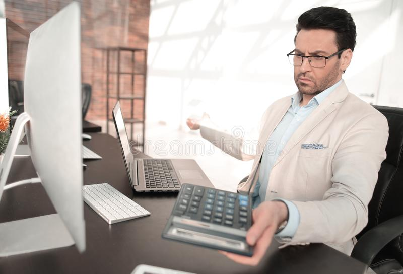 Behind the glass.serious businessman with calculator sitting at his Desk stock photos