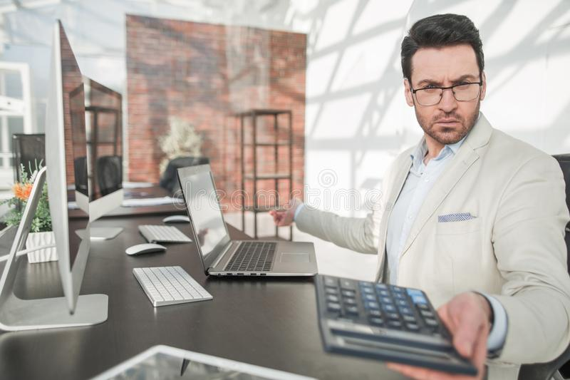 Behind the glass.serious businessman with calculator sitting at his Desk stock photography