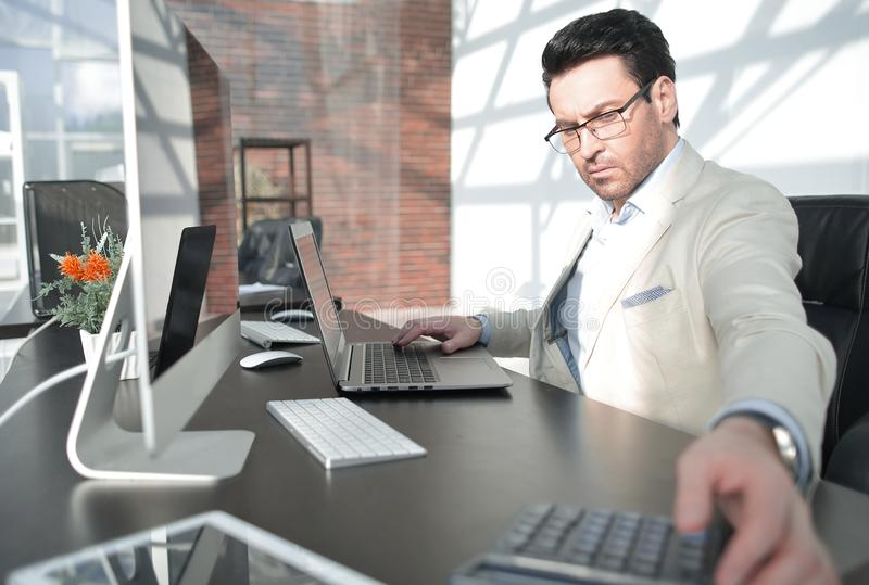 Behind the glass.serious businessman with calculator sitting at his Desk stock photo