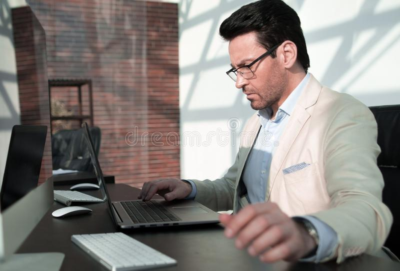 Behind the glass.serious businessman with calculator sitting at his Desk royalty free stock photo
