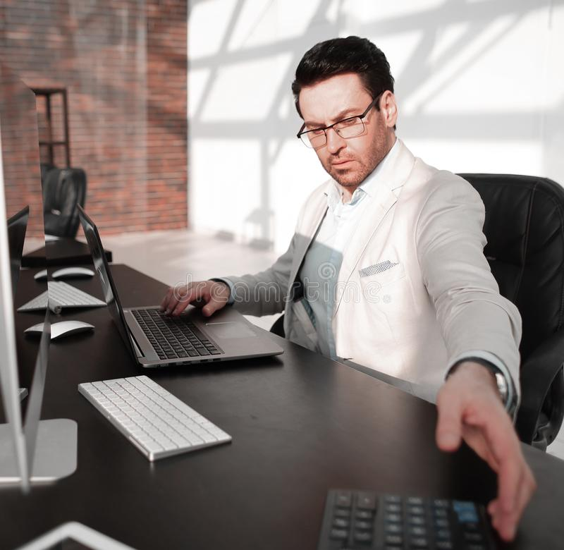 Behind the glass.serious businessman with calculator sitting at his Desk royalty free stock image
