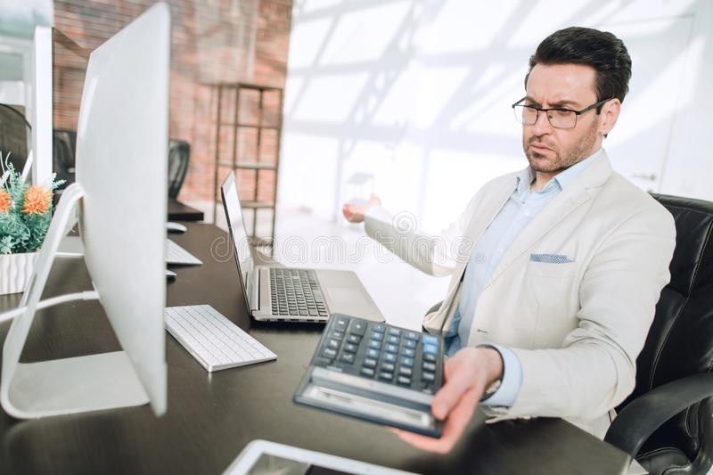 Behind the glass.serious businessman with calculator sitting at his Desk stock image