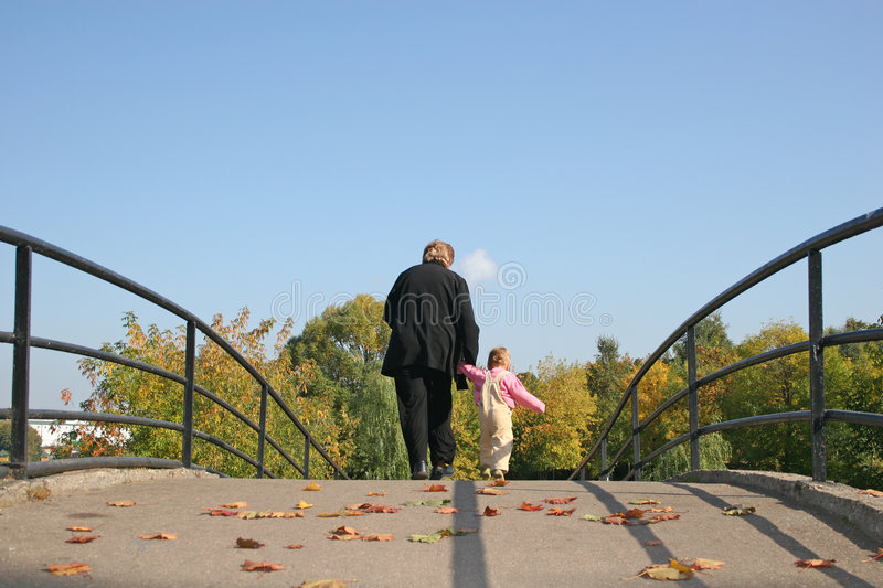 Behind grandmother and baby. On autumn bridge stock photo