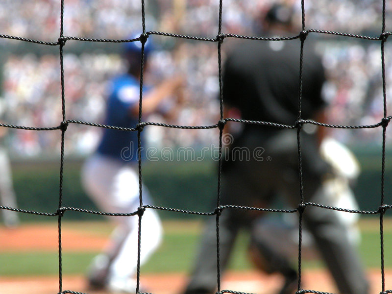 Behind Home Plate. Looking through the fence behind home plate at a Chicago Cubs game