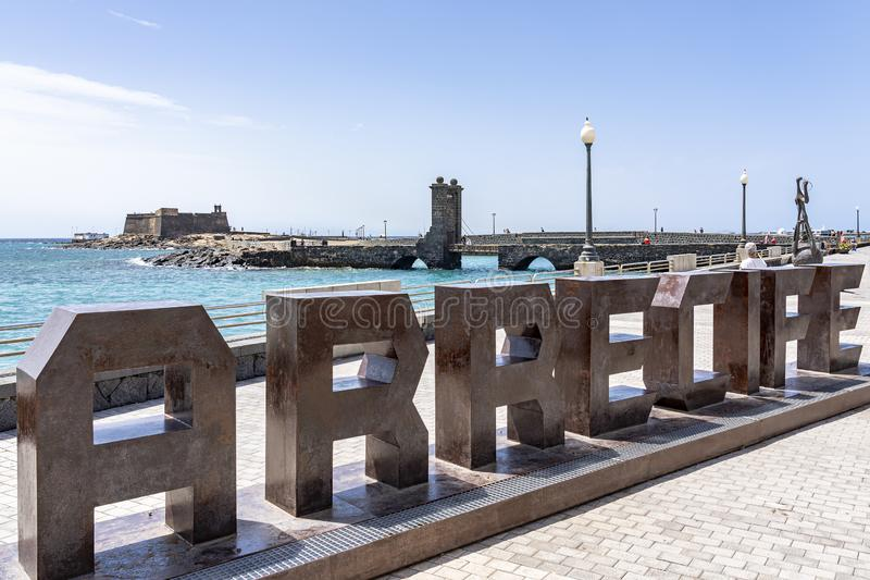 Behind the letters of the capital of Lanzarote Arrecife you see the old fortress Castillo de San Gabriel, Lanzarote, Spain royalty free stock photography