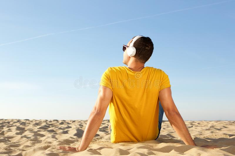 Behind of man sitting on beach listening to music looking at the sky. Portrait from behind of man sitting on beach listening to music looking at the sky stock image